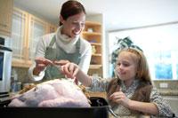 ターキーを一緒に料理する母親と娘
