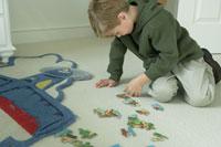 子供部屋でパズルをして遊ぶ少年