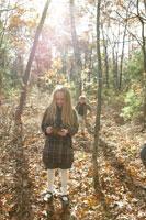 秋の森林を散歩する少女と少年