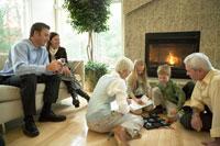 暖炉のあるリビングルームでくつろぐ家族