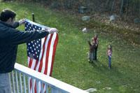 星条旗をかざす父親に手を振る母と子供達 24003000190| 写真素材・ストックフォト・画像・イラスト素材|アマナイメージズ
