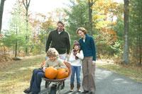 かぼちゃと息子を運ぶ父と供に歩く母と娘