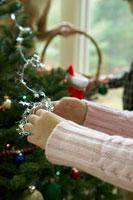クリスマスツリーの飾りつけをする少女