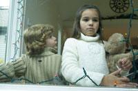 縫いぐるみを抱っこして窓際に立つ子供達