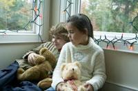 縫いぐるみを抱っこして窓際に座る子供たち