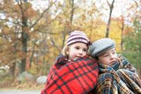 紅葉の森でブランケットに包まる少年と少女 24003000254A  写真素材・ストックフォト・画像・イラスト素材 アマナイメージズ