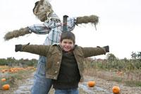 かぼちゃ畑でかかしと遊ぶ少年 24003000258| 写真素材・ストックフォト・画像・イラスト素材|アマナイメージズ