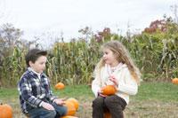 かぼちゃの上に座って遊ぶ少年と少女
