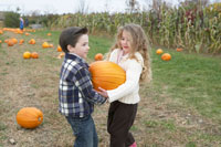 大きなかぼちゃを運ぶ少年と少女