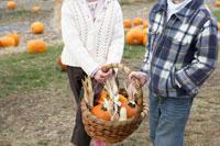 かぼちゃの入ったかごを持つ少年と少女