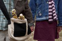 乾燥とうもろこしを鞄で運ぶ少年と少女