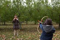 少女の頭の上のりんごを弓矢で狙う少年