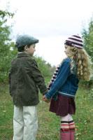 りんご畑を手を繋いで散歩する少年と少女
