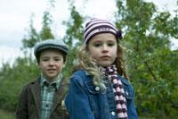 りんご畑に立つ少女と少年