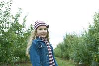 りんご畑に立つ少女 24003000313| 写真素材・ストックフォト・画像・イラスト素材|アマナイメージズ