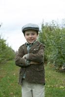 りんご畑で腕を組んで立つ少年 24003000314| 写真素材・ストックフォト・画像・イラスト素材|アマナイメージズ
