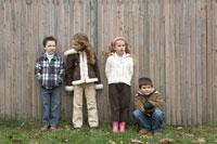 木のフェンス際に並ぶ子供達