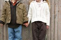木のフェンス際で手を繋ぐ少年と少女
