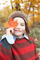 落ち葉を目にあてて遊ぶ少年 24003000327B  写真素材・ストックフォト・画像・イラスト素材 アマナイメージズ