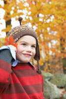 落ち葉を耳にあてて遊ぶ少年 24003000327D| 写真素材・ストックフォト・画像・イラスト素材|アマナイメージズ