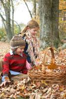 かごに落ち葉を入れる少年と少女