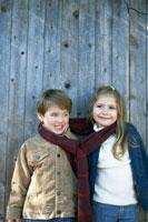 マフラーを一緒に首に巻く少年と少女 24003000337A| 写真素材・ストックフォト・画像・イラスト素材|アマナイメージズ