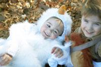 ハロウィーン衣装を着て落ち葉の上で遊ぶ子供達