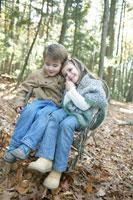 一つの椅子に仲良く座る少年と少女