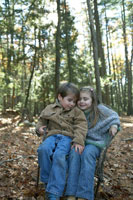 一つの椅子に仲良く座る少年と少女 24003000361C| 写真素材・ストックフォト・画像・イラスト素材|アマナイメージズ