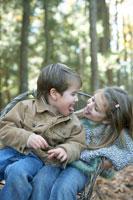 一つの椅子に座って遊ぶ少年と少女 24003000362| 写真素材・ストックフォト・画像・イラスト素材|アマナイメージズ