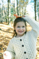 落ち葉を持って遊ぶ少女 24003000366| 写真素材・ストックフォト・画像・イラスト素材|アマナイメージズ
