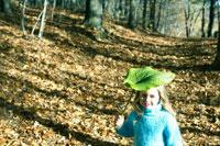 葉っぱを持って森を散歩する少女 24003000368| 写真素材・ストックフォト・画像・イラスト素材|アマナイメージズ