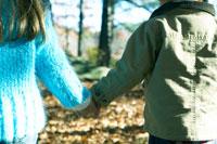 落ち葉の中を手を繋いで歩く少年と少女