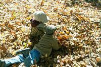 落ち葉の中で遊ぶ少年達