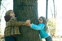 木の幹を両手で抱える少年と少女