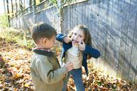 外でにらめっこをして遊ぶ少女と少年