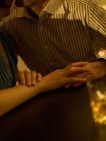 バーで手を握りあう白人カップル