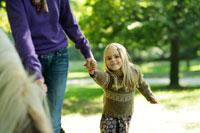 北欧の森で母親の手を繋ぐ少女