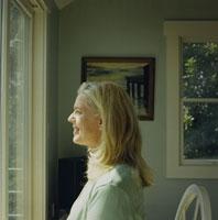 笑顔で窓際に立つ女性