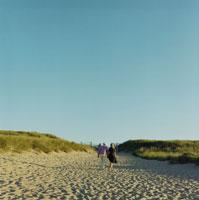 手を繋いで海岸を散歩する夫婦