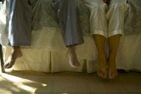 ベッドに並んで座る夫婦の足 24007000035A| 写真素材・ストックフォト・画像・イラスト素材|アマナイメージズ
