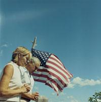 アメリカ国旗の前で祈りを捧げる夫婦