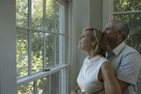 窓越しの風景を眺める夫婦