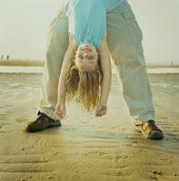 海岸で父親に逆さ抱っこされる娘 24007000112| 写真素材・ストックフォト・画像・イラスト素材|アマナイメージズ