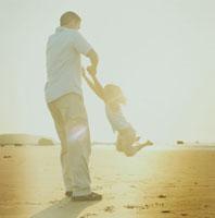 海岸で父親にぶら下がって遊ぶ娘