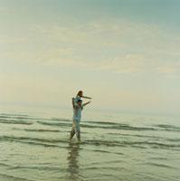 海岸で娘を肩車して散歩する父