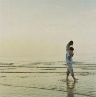 海岸で娘を肩車して散歩する父 24007000121| 写真素材・ストックフォト・画像・イラスト素材|アマナイメージズ
