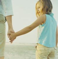 海岸で手を繋ぎあって遊ぶ母と娘