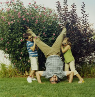 芝生で逆立ちをする父と足を支える息子と娘