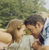 テーブルの上で額を付き合わせる父親と娘 24007000156| 写真素材・ストックフォト・画像・イラスト素材|アマナイメージズ